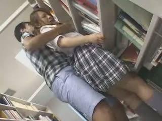 Ντροπαλός/ή κορίτσι του σχολείου χουφτωμένος/η και used σε ένα βιβλιοθήκη