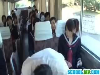 Adolescente en un público autobús puts su cara en un autobús rider lap