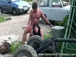Pieptoasa bruneta gets inpulit împotriva an vechi masina de antic dude