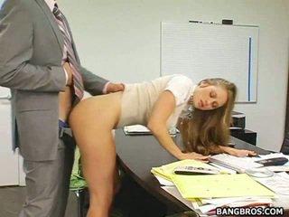 Blonde secretary bent over her desk an...