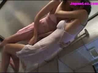 2 meisjes in nat clothes kussen patting onder de douche